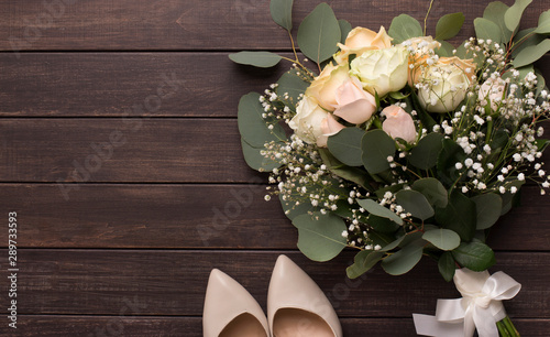 Fototapeta Wedding bouquet and high heel shoes for bride on wood obraz
