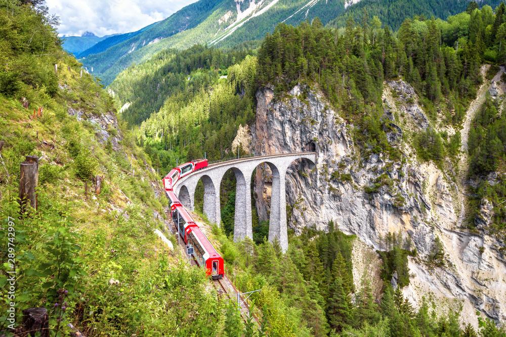 Fototapety, obrazy: Landwasser Viaduct in Filisur, Switzerland. It is famous landmark of Swiss. Mountain landscape with red train of Bernina Express on high bridge. Scenic view of amazing Alpine railway in summer.