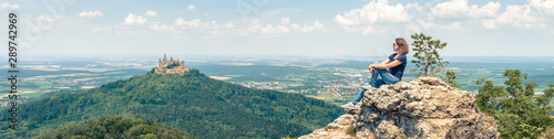 Obraz Landscape with young woman and Hohenzollern Castle, Germany. This place is a famous tourist attraction of Swabia. Adult girl travels in Alpine mountains in summer. Wide panorama of castle and person. - fototapety do salonu