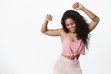 Fun, party, wellbeing concept. African-american curly-haired girl in trendy pink top, skirt dancing with hands spread air, smiling broadly close eyes as enjoying music with carefree expression