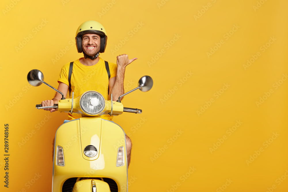 Fototapeta People, transport and advertisement concept. Cheerful young European male motorcyclist points thumb away, dressed casually, poses on own motorbike, glad to show copy space for your information