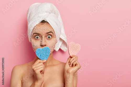Fotografía  Headshot of surprised young lady with bugged eyes, wears white towel on wet head