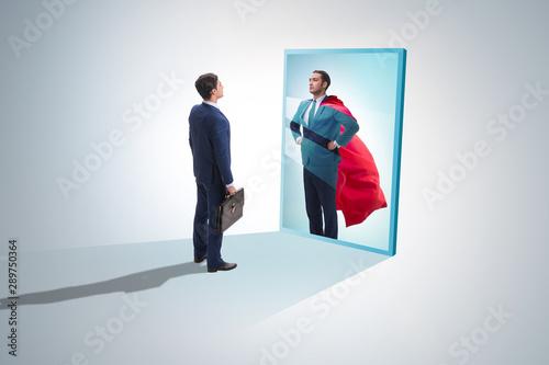 Fotomural  Businessman seeing himself in mirror as superhero