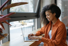 Happy African American Woman Copywriter Working Freelance Project In Modern Cafe. Businesswoman Using Laptop, Searching Information On Website. Successful Business. Online Training Courses Concept