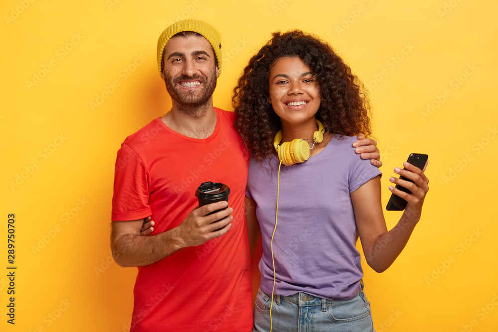 Fototapety, obrazy: Photo of happy mixed race couple spend free time together, drink coffee and use modern cellular for online communication, dressed in t shirts, stand closely to each other against yellow background