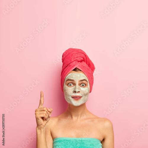 Recess Fitting Spa Beauty and spa concept. Photo of lovely woman points index finger above, wears nourising mask, reduces pimples, avoids problems of skin dryness, wrapped in bath towel, isolated on pink wall.