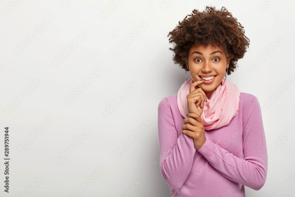 Fototapety, obrazy: Studio shot of happy Afro woman with curly hairstyle, touches index finger on lips, has toothy smile, dressed casually, looks straightly at camera, stands against white background, copy space for text