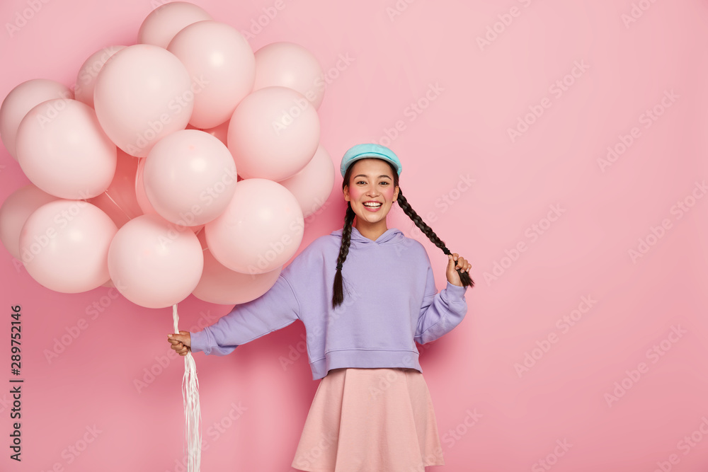 Fototapety, obrazy: Pretty cheerful Asian teenage girl comes on holiday with bunch of airballoons, has two dark long plaits, rouge cheeks and minimal makeup, wears oversized purple jumper and skirt, being in good mood