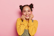 Portrait Of Beautiful Asian Girl With Pinup Makeup, Holds Chin With Both Hands, Dressed In Casual Outfit, Has Dark Hair Combed In Two Buns, Poses Against Rosy Background, Wears Piercing In Nose
