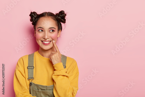 Fotografie, Tablou  Pretty young woman with Asian appearance, wears yellow sweatshirt and overalls, has two hair buns, looks aside, models against pink background, blank space for promo