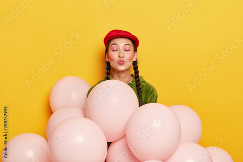 Studio shot of pleased woman with pink makeup, keeps lips rounded, wants to kiss Canvas Print