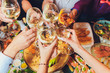 Leinwanddruck Bild - Close up shot of group of people clinking glasses with wine or champagne in front of bokeh background. older people hands