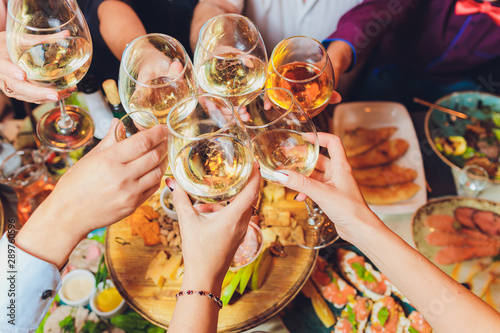 Close up shot of group of people clinking glasses with wine or champagne in front of bokeh background. older people hands - 289760596