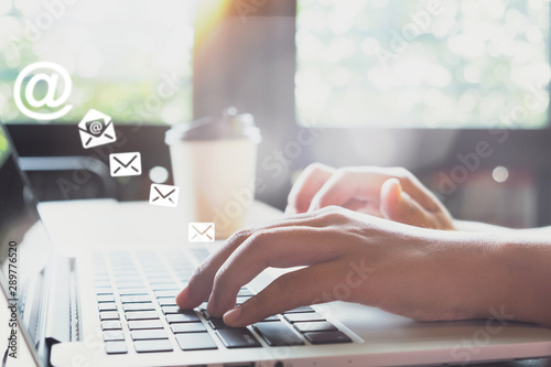 Hand of female using laptop computer sending e-mail message with email address symbol and envelope icon Wallpaper Mural