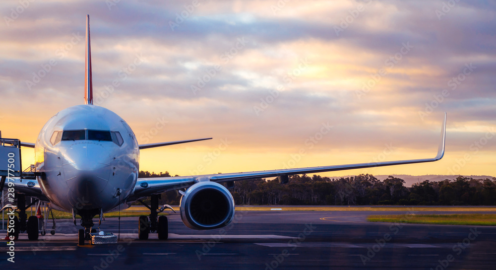 Fototapeta Sunset view of airplane on airport runway under dramatic sky in Hobart,Tasmania, Australia. Aviation technology and world travel concept.