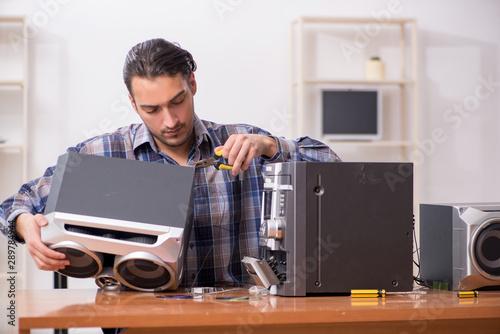 Fotomural  Young engineer repairing musical hi-fi system