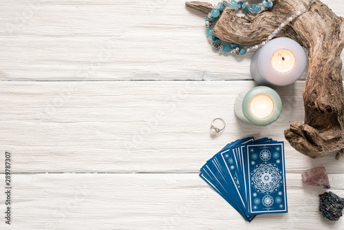 Foto Blue tarot cards on white wooden table background.