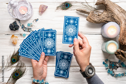 Fotografia  Fortune teller woman and a blue tarot cards over white wooden table background