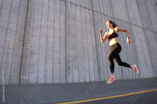 fototapeta na drzwi i meble Young attractive woman with perfect slim body running outdoors. Fitness and running concept