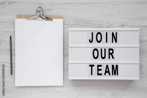 Cuadros en Lienzo  'Join our team' words on a lightbox, clipboard with blank sheet of paper on a white wooden background