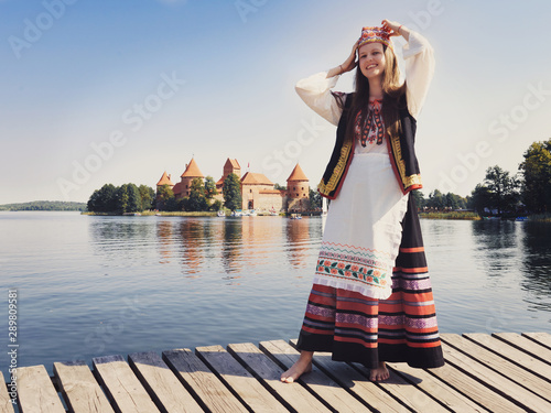 Beautiful girl in national dress in an ancient medieval castle in Trakai in Lithuania. Retro photography. Restoring the atmosphere of the Middle Ages.