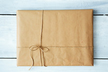 Close Up Christmas Style Rustic Brown Paper Package Tied Up With Strings. White Wood Floor Background.