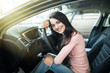 Portrait of beautiful young woman sitting in a new car and smiling in showroom