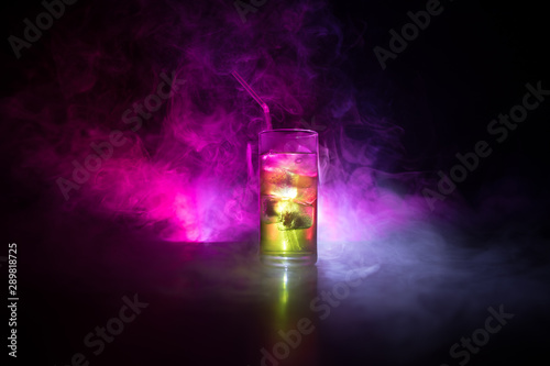 In de dag Alcohol Cocktail glass splashing on dark toned smoky background or colorful cocktail in glass. Party club entertainment. Mixed light.