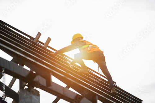 Fotografia  Roof repairman, construction engineer wearing safety inspection kit in Asia