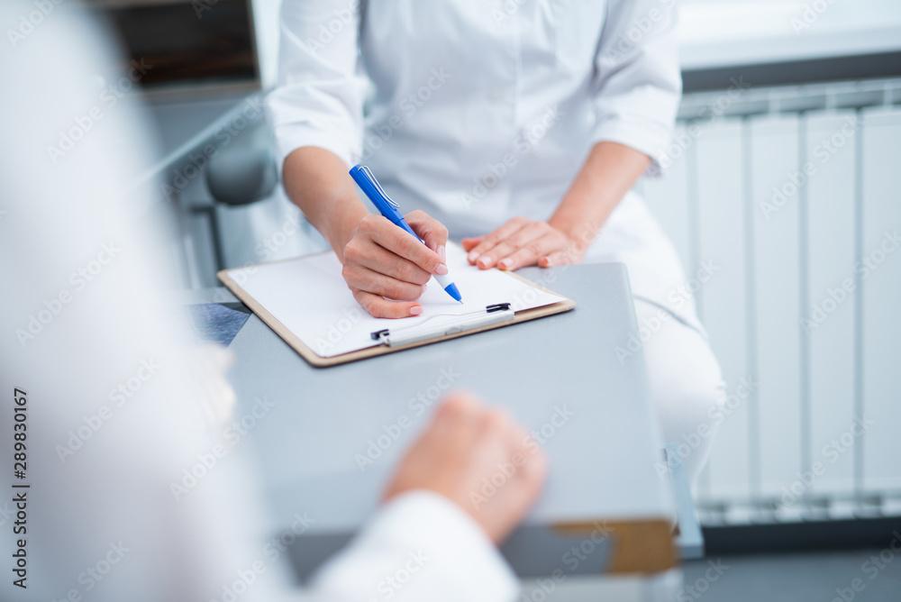 Fototapeta Dentist is filling out a patient questionnaire
