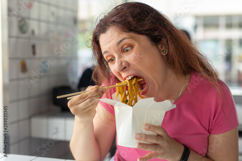 Valokuva  Close-up portrait of an amusing crazy young pretty girl eating chinese noodles with wooden chopsticks sitting in a cafe