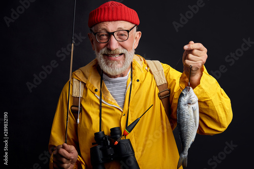 old experienced happy fisherman in glasses holding a fish and a fishing rod isolated on black background Canvas Print