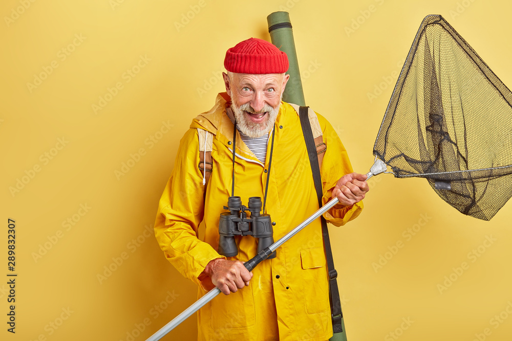 Fototapety, obrazy: man is crazy about fishing . positive feeling and emotion. necessary equipment. professional fishman with binocular and equipment going to river. close up photo. isolated yellow background