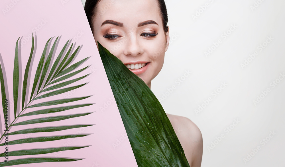 Fototapety, obrazy: Portrait of young beautiful woman with healthy glow perfect smooth skin holds green tropical leaf. Model with natural nude make up look into the hole of pink paper. Gray background.