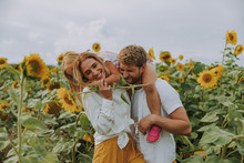 Young Family Laughing Together In Sunflower Field In Summer