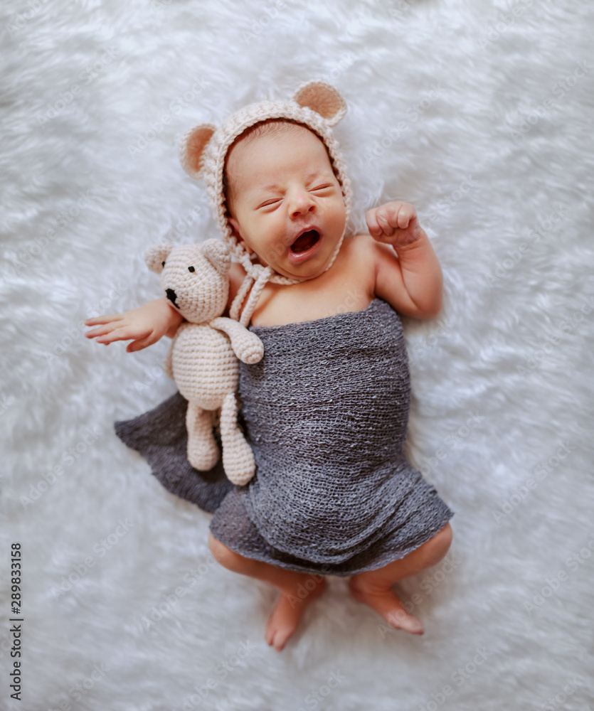 Fototapeta Top view of sleepy newborn boy wrapped in gray scarf and with little cap hugging knitted bear and yawning.