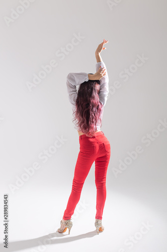 Latina dance, strip dance, contemporary and bachata lady concept - Woman dancing improvisation and moving her long hair on a white background - 289834543