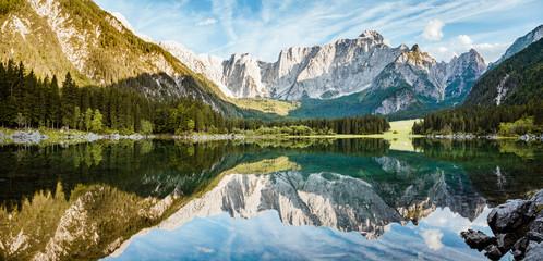 Fototapeta Optyczne powiększenie Alpine peaks reflecting in tranquil mountain lake at sunrise