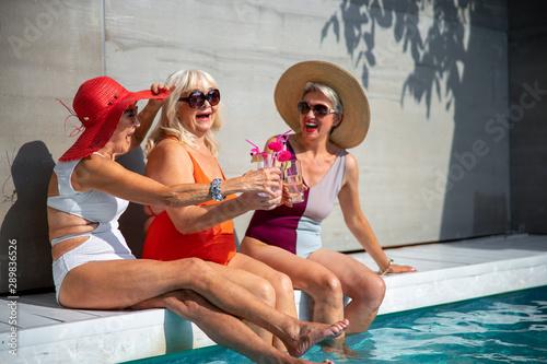 Fotografia Joyful old women toasting with cocktails stock photo