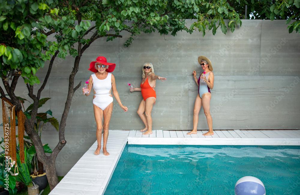 Fototapeta Cheerful old women walking on the edge of swimming pool