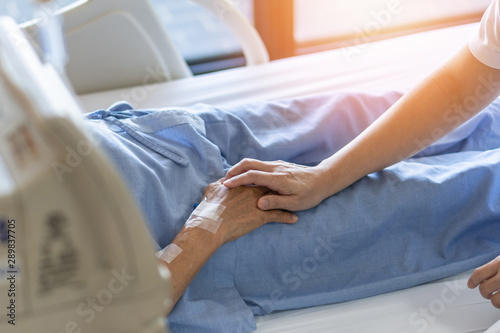 Fotografía Caregiver holding elderly senior patient (ageing old adult person) hand in hospi