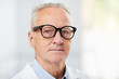 Leinwandbild Motiv Head and shoulders portrait of white haired senior doctor wearing glasses and looking at camera while posing in office, copy space