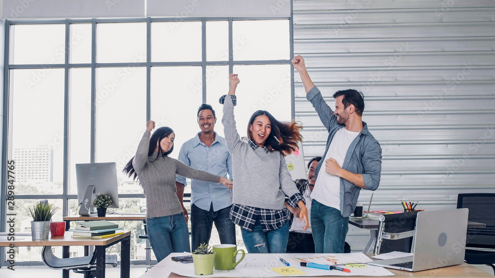 Fototapeta group of creative designer dancing in office with relax feeling and glad about good success news of project at modern office.business day work lifestyle.