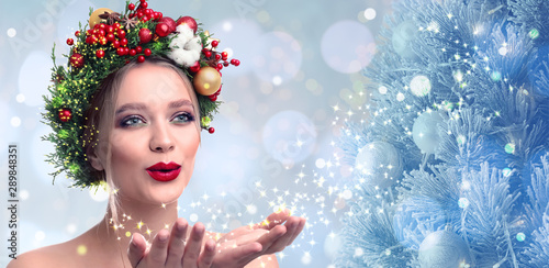 Fototapeta Beautiful young woman with Christmas wreath blowing magical snowy dust on blurred background. Bokeh effect obraz