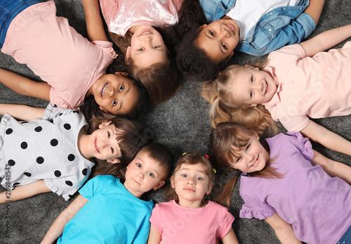 Fototapeta Adorable little children lying on floor together indoors, top view. Kindergarten playtime activities obraz na płótnie