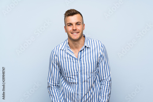 Young handsome blonde man over isolated blue background laughing