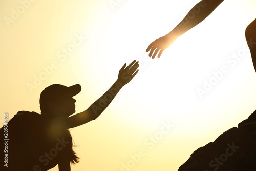 Silhouettes of man and woman helping each other to climb on hill against sunset Canvas Print