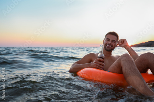Poster de jardin Bar Happy young man with drink on inflatable ring in water
