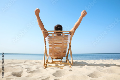 Stampa su Tela Young man relaxing in deck chair on sandy beach