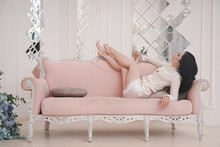 Lovely Brunette Woman In White Cute Pyjama Rest With Pink Sofa Alone In White Apartment Alone